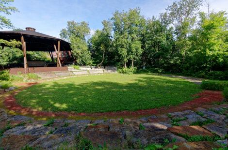 Le cercle de danse PowWow se présente comme un amphithéâtre de verdure, il est composé de trois anneaux traités en trois matériaux distincts : L'herbe pour l'espace de danse, la pierre et la terre battue marquant la limite avec les spectateurs.